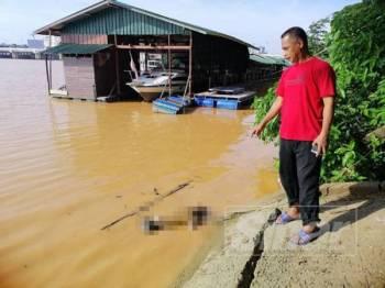 Penduduk Kampung Pasir Pekan, Mohd Nasir Abdul Kadir, 53, menunjukkan mayat warganegara Thailand yang ditemui terapung ditarik dengan bot ke jeti Pasir Pekan.