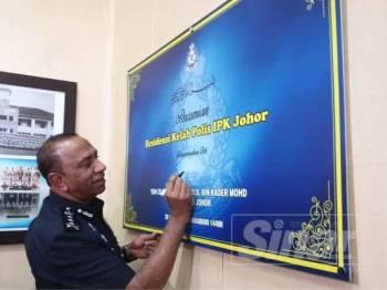 Ketua Polis Johor, Datuk Mohd Khalil Kader Mohd menandatangani plak perasmian bangunan Residensi Kelab Polis IPK Johor di sini hari ini.