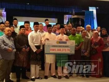 Abdul Basith (empat, kanan) dan Aziudin(lima, kanan) menerima zakat perniagaan sebanyak RM5.4 juta yang dibayar oleh 52 syarikat.