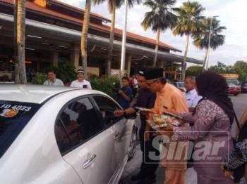 Ahmad Ishak (tengah) mengedarkan goodies beg kepada pengguna di hentian tersebut, kelmarin.