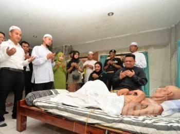 Mohd Nazim (dua dari kiri) mengetuai bacaan doa memohon kesembuhan salah seorang pesakit yang diziarahi baginda berdua semalam.