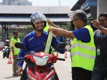 Ir Rostam memakaikan jaket kenderaan kepada pengguna motosikal sempena Pelancaran Kempen Keselamatan Balik Raya PROLINTAS sempena sambutan Aidilfitri di Plaza Tol Datuk Keramat (arah Ampang) AKLEH hari ini.
