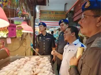 Muhamad Zikril memantau harga ayam yang disenarai sebagai barang kawalan SHMMP di Pasar Awam Kajang semalam.