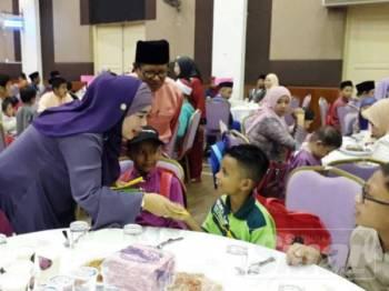 Halimaton Shaadiah (tengah) menyantuni 207 anak-anak yatim dan OKU bersama pelajar tahfiz di Dewan Seri Mentaloon, di sini, malam tadi.