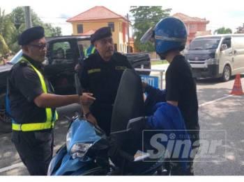Mohd Apandi (tengah) bersama anggota memeriksa lesen dan cukai jalan seorang penunggang motosikal.