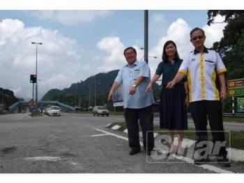 Boon Chye (kanan) bersama Thomas Su dan Sandrea Ng menunjukkan jalan yang akan diselenggara ketika melawat kawasan berhampiran persimpangan tol Gopeng, di sini hari ini.