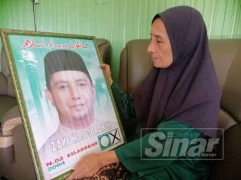 Che Zaharah menatap gambar arwah Mohd Zaki ketika awal penglibatannya dalam politik menjadi calon PAS di DUN Kelaboran pada tahun 2004.