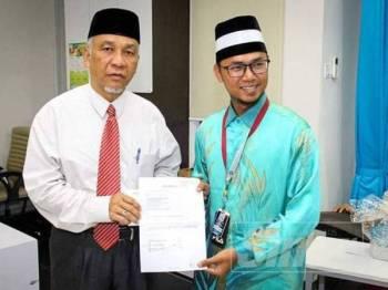 Ami Nardin menyerahkan cek RM80,000 kepada Muhammad Hafiz bagi pembelian dua mesin hemodialisis.