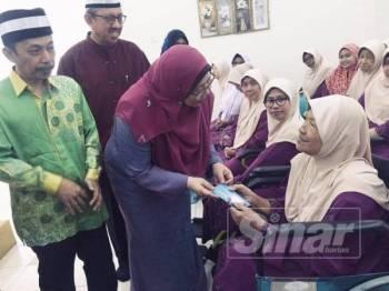 Fuziah (tengah) menyampaikan sumbangan kepada penghuni warga emas Kompleks Asnaf MUIP hari ini.