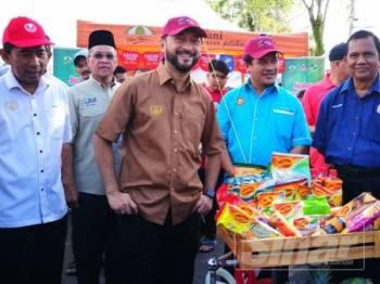 Mukhriz (dua dari kiri) selepas gimik pelancaran Jualan Harapan Rakyat Pra-Syawal peringkat negeri, yang diadakan di Pasar Tani Taman Wira Mergong.