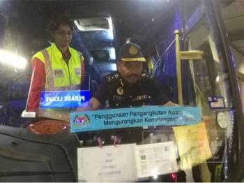 Mohamat Johari melekatkan pelekat kempen keselamatan jalan raya pada sebuah bas bersempena dengan Ops Hari Raya Aidilfitri semalam.