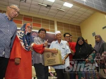 Ahmad Faizal (lima kanan), menyampaikan sumbangan kepada peserta Felcra pada program berkenaan.