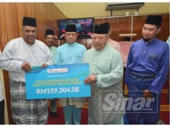 Tuanku Syed Sirajuddin (dua dari kanan) perkenan menerima zakat perniagaan Bank Muamalat Malaysia Berhad yang disampaikan oleh Mohd Redza Shah. Turut berangkat Tuanku Syed Faizuddin (tiga dari kiri).