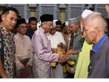 Perdana Menteri Tun Dr Mahathir Mohamad diiringi Ketua Menteri Sabah Datuk Seri Mohd Shafie Apdal (dua, kiri) ketika menyampaikan sumbangan kepada seramai 20 golongan Asnaf pada majlis Iftar bersama Perdana Menteri di Masjid Bandaraya di sini hari ini.