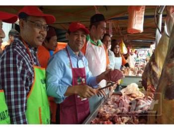 Abdul Yunus memotong daging untuk dijual kepada pengunjung pasar tani dalam jualan happy hour pada Majlis Pelancaran Program Jualan Jimat Belanja Aidilfitri @ Pasar Tani di Pasar Tani Masjid Sultan Nazrin Muizzuddin Shah, di Tapah hari ini.