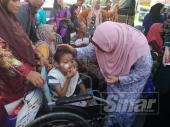 Fuziah beramah mesra bersama kanak-kanak OKU ketika menyampaikan sumbangan duit raya pada Majlis Pelancaran Pasar Tani Khas Pra Syawal Peringkat Negeri Pahang di sini semalam.