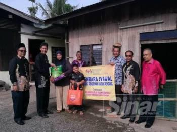 Wakil PPD Pendang menyampaikan sumbangan kepada keluarga salah seorang pelajar.