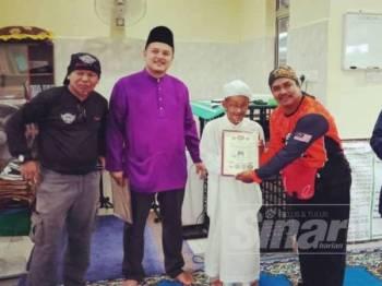 Tamizi (kanan) menyerahkan sijil kepada Imam Masjid Paya Besar di Surau Bukit Pak Kuning baru-baru ini.