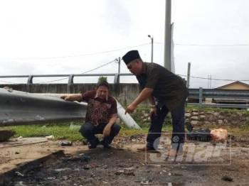 Pengerusi Majlis Pengurusan Komuniti Kampung (MPKK) Kampung Tengah, Amer Md Nor (kanan) menunjukkan kepada ADUN Klebang Gue Teck kedudukan tong sampah dan bekas kebakaran yang dilakukan oleh pencari barangan lusuh.