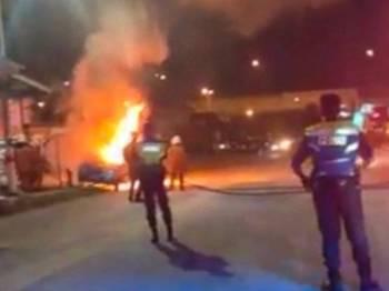 Anggota bomba membantu memadam kereta yang terbakar.