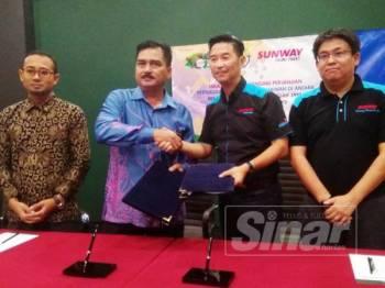 Mohd. Rafee bertukar dokumen MoU bersama Pengurus Besar Kanan Sunway Theme Park, Calvin Ho (dua dari kanan).