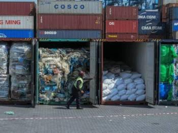 Pekerja kontraktor membuka kontena yang mengandungi bahan buangan ketika liputan menghantar semula sisa plastik kepada pengeksport di Pelabuhan Barat baru-baru ini. - FOTO BERNAMA