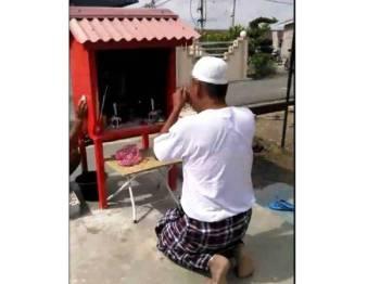 Rakaman gambar dari klip video tular dalam Facebook menunjukkan aksi suspek berpakaian kain pelekat dan kopiah menjalani aktiviti pemujaan tokong Dato Kong di Taman Piandang Indah, Tanjung Piandang baru-baru ini.