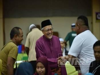 Tengku Hassan (tengah) beramah mesra bersama tetamu yang hadir sempena Majlis Jamuan Hari Raya DUN Ladang di Stadium Negeri.