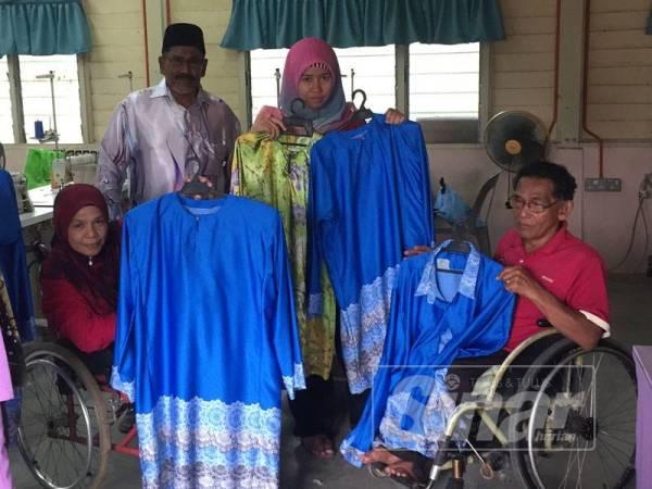 Harunarrsheed (dua dari kiri) bersama pekerja OKU yang mahir dalam bidang jahitan menunjukkan baju yang mereka jahit.