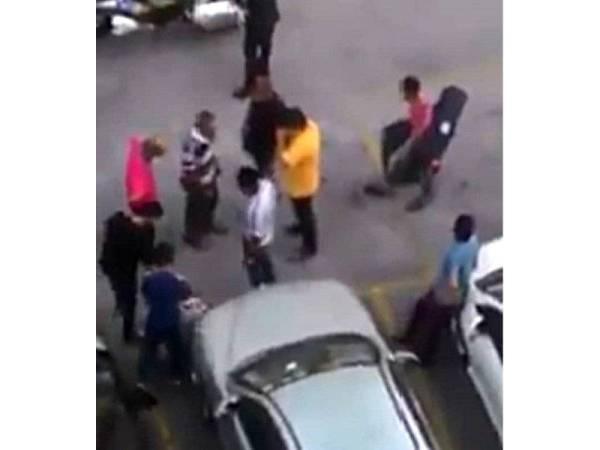 Tangkkap layar dari video tular yang menunjukkan orang awam menahan lelaki Pakistan sebelum diserahkan kepada polis.