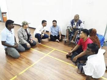 Mohd Faizal (empat, kiri) berbincang sesuatu dengan ADUN Jeram, Shaid Mohd Rosli ketika kunjungan meninjau mangsa banjir di PPS Dewan MDKS Desa Coalfields.