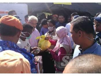 Dr Wan Azizah (tengah) menyerahkan bantuan makanan kepada orang asli di sini.
