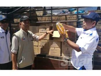 Muez (kanan) menunjukkan sebahagian bantuan makanan dan keperluan harian untuk manfaat orang asli di perkampungan orang asli Kuala Koh hari ini.