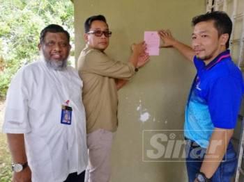 Mohd Khuzzan (tengah) menampal notis di sebuah rumah kosong sambil diperhatikan oleh Dr Sellahuddeen (kiri) dan Mohd Syukri di Taman Sri Lambak, Kluang.