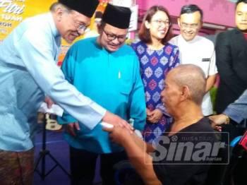 Anwar menyampaikan sumbangan duit raya kepada salah seorang Orang Kurang Upaya (OKU) ketika menghadiri Majlis Rumah Terbuka Adilfitri Parlimen Hang Tuah Jaya di Kota Fesyen di Ayer Keroh, di sini, hari ini.
