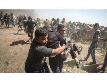 Penduduk Palestin mengangkat rakan mereka yang cedera akibat ditembak tentera Israel.
