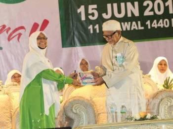 Nuridah menyampaikan karya terbaharu Muslimat Pas kepada Presiden Pas, Datuk Seri Abdul Hadi Awang yang hadir merasmikan Muktamar Tahunan Dewan Muslimat Pas Kali Ke-59 di Bukit Gambang Resort City hari ini.
