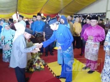 Sultan Selangor berkenan menyampaikan sumbangan duit raya kepada penerima.