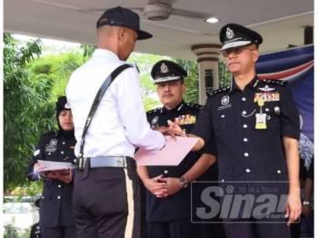 Hasanuddin (kanan) menyampaikan sijil penghargaan kepada anggotanya dalam Perhimpunan Bulanan di IPK Kelantan hari ini.