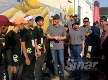 Kar Hing (lima dari kiri), berkata sesuatu kepada kumpulan pelajar yang terlibat dalam proses menyiapkan mural di Lorong Hill.