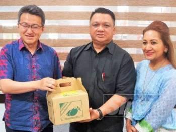 Senator Chin Tong (kiri) menerima buah Harumanis sebagai cenderahati daripada Tuanku Syed Faizuddin.