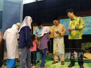 Akmal (dua,kanan) menyampaikan duit raya kepada kanak-kanak yang menghadiri Majlis Sambutan Hari Raya dan Rumah Terbuka Parlimen Johor Bahru di sini, hari ini.