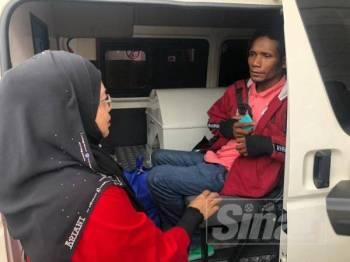Dr Selasawati (kiri) sempat mengiringi yang Rosli menaiki van bagi menemani mayat anaknya yang dibawa ke HGM pada tengah hari ini.