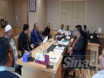 Abu Bakar Yahya (empat dari kiri) meneliti dokumen berkaitan isu teksi sambil diperhatikan oleh Datuk Mohamad Dahlan Md. Maamor di Kementerian Pengangkutan, Putrajaya hari ini.