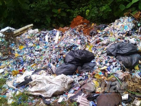 Sisa buangan plastik yang turut dibuang di tepi kawasan masuk ke tapak pembuangan sampah haram berkenaan.