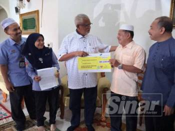 Mahfuz menyampaikan replika cek Faedah Pengurusan Mayat kepada Mohd Nor di Kampung Pangkal Binjal, Batu 31, di sini hari ini.