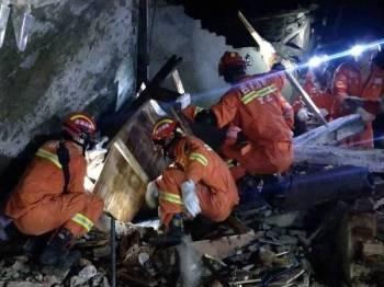 Pasukan bomba bertungkus-lumus mengeluarkan mangsa yang terperangkap di bawah runtuhan bangunan.