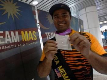 Atlet memanah negara Khairul Anuar Mohamad bergambar bersama pingat perak yang berjaya diraihnya sewaktu tiba di Lapangan Terbang Antarabangsa Kuala Lumpur (KLIA) hari ini. - Foto Bernama
