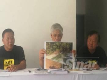 Bun Teet (tengah) menunjukkan gambar Sungai Balok yang terletak berdekatan kolam air sisa buangan Lynas pada sidang media hari ini.