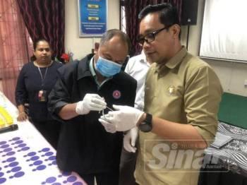 Mohd Khuzzan (kanan) ketika melihat salah satu sampel air kencing yang diambil daripada sebahagian pelajar sekolah menengah di negeri ini.